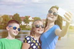 La compañía alegre del ` s de los niños hace el selfie en un smartphone en una calle de la ciudad al aire libre Foto de archivo
