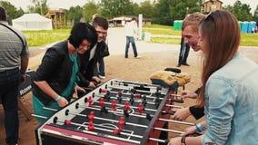 La compañía de amigos absorbedly juega a fútbol americano de la tabla Festival del verano almacen de video