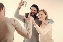 La compañía de amigos alegres pasa ocio con las bebidas Los individuos sostienen la taza, frasco con alcohol, hablan Hombres, muj fotos de archivo
