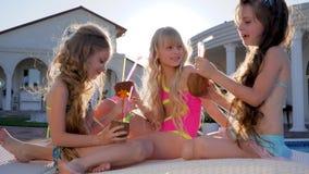 La compañía de amigos felices con los cocos en manos se relaja por la piscina, cóctel de pequeñas novias, niñez feliz almacen de metraje de vídeo