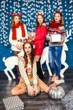 La compañía de cuatro muchachas hermosas en el fondo de Christm Imagen de archivo libre de regalías