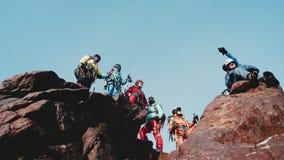 La compañía de escaladores se coloca encima de la montaña, disfrutando y sonriendo para aumentar sus manos el operador quita almacen de metraje de vídeo