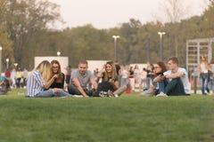 La compañía de la gente joven que se sienta en el césped verde en la abertura de un nuevo parque moderno en la ciudad en la época Fotos de archivo libres de regalías