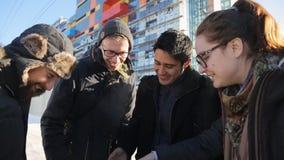 La compañía de la gente feliz se coloca en la calle fría del invierno en tiempo del día almacen de video