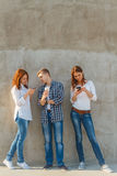 La compañía de la gente joven con el teléfono Imágenes de archivo libres de regalías