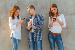 La compañía de la gente joven con el teléfono Fotografía de archivo