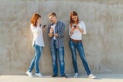 La compañía de la gente joven con el teléfono Imagen de archivo libre de regalías