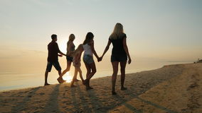 La compañía de niños y los adultos se están divirtiendo en la playa, llevando a cabo las manos almacen de metraje de vídeo