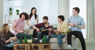 La compañía grande atractiva de étnico multi de los amigos tiene un buen rato junto en la sala de estar, algo del individuo en el almacen de video