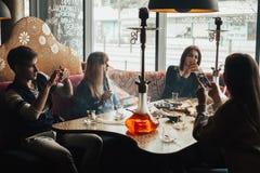 La compañía joven se está divirtiendo y está comiendo en barra fumar una cachimba, comunicando en un restaurante oriental imagen de archivo