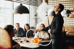 La compañía joven se está divirtiendo y está comiendo en barra fumar una cachimba, comunicando en un restaurante oriental imagen de archivo libre de regalías