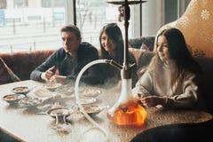 La compañía joven se está divirtiendo y está comiendo en barra fumar una cachimba, comunicando en un restaurante oriental foto de archivo