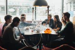 La compañía joven se está divirtiendo y está comiendo en barra fumar una cachimba, comunicando en un restaurante oriental fotos de archivo libres de regalías