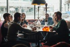 La compañía joven se está divirtiendo y está comiendo en barra fumar una cachimba, comunicando en un restaurante oriental imagenes de archivo