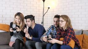 La compañía multinacional se sienta en el sofá, muchachas que juegan fps del juego 50 de la consola