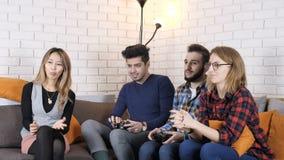 La compañía multinacional se sienta en el sofá, muchachos que juegan fps del juego 50 de la consola