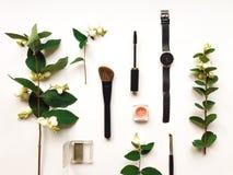 La composición colorida con la mujer compone las herramientas y los accesorios, adornados con las ramas verdes del snowberry Ende Foto de archivo