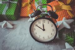 La composición con las cajas de regalo, reloj del día de fiesta de la Navidad y del Año Nuevo, protagoniza en el fondo gris Copys Imágenes de archivo libres de regalías