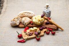 La composición con queso junta las piezas en aceite, aceitunas y pimientos picantes de oliva Foto de archivo