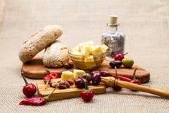 La composición con queso junta las piezas en aceite, aceitunas y pimientos picantes de oliva Fotografía de archivo