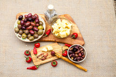 La composición con queso junta las piezas en aceite, aceitunas y pimientos picantes de oliva Imágenes de archivo libres de regalías