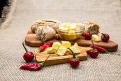 La composición con queso junta las piezas en aceite, pan y pimientos picantes de oliva Fotografía de archivo libre de regalías