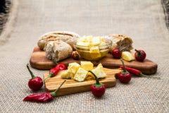 La composición con queso junta las piezas en aceite, pan y pimientos picantes de oliva Imágenes de archivo libres de regalías