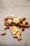 La composición con queso junta las piezas en aceite, pan y pimientos picantes de oliva Foto de archivo libre de regalías