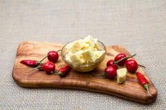La composición con queso junta las piezas en aceite y pimientos picantes de oliva Foto de archivo libre de regalías