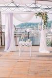 La composición de la boda de la pequeños tabla y arco blancos adornados con las flores coloridas Imágenes de archivo libres de regalías