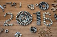 La composición 2016 de la Feliz Año Nuevo con los tornillos clava los pernos y los pasadores Foto de archivo libre de regalías