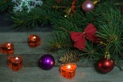 La composición de la Navidad de las ramas del abeto adornó arcos y bolas con las velas ardientes en un fondo de madera Imágenes de archivo libres de regalías