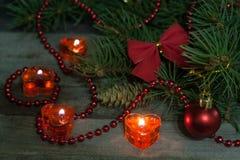 La composición de la Navidad de las ramas del abeto adornó arcos y bolas con las velas ardientes en un fondo de madera Imagen de archivo libre de regalías