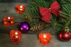 La composición de la Navidad de las ramas del abeto adornó arcos y bolas con las velas ardientes en un fondo de madera Foto de archivo libre de regalías