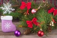 La composición de la Navidad de las ramas del abeto adornó arcos y bolas con los calcetines en un fondo de madera Fotos de archivo libres de regalías