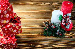 La composición de las tres velas, adornada con una puntilla del abeto con los conos y los regalos en superficie de madera Imagen de archivo libre de regalías