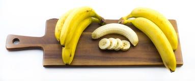 La composición de los plátanos uno de ellos se pela y corte en un tablero de madera y un fondo blanco Fotografía de archivo
