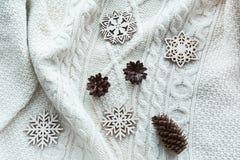 La composición de la Navidad con el cono, copos de nieve en blanco hizo punto el suéter Tarjeta del día de fiesta Estilo de la ve Imágenes de archivo libres de regalías