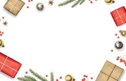 La composición de la Navidad con las cajas de regalo, las decoraciones, las ramas de árbol de navidad y las bayas rojas enmarcó e Fotos de archivo libres de regalías
