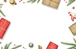 La composición de la Navidad con las cajas de regalo, las decoraciones, las ramas de árbol de navidad y las bayas rojas enmarcó e Imágenes de archivo libres de regalías