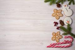 La composición de la Navidad con los bastones de caramelo, las ramas de árbol de abeto y el jengibre empanan las galletas Imagenes de archivo