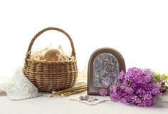 La composición de Pascua con los huevos en una cesta de mimbre, un icono y un campo florece Imagen de archivo libre de regalías