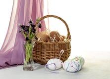 La composición de Pascua con los huevos en una cesta de mimbre y un campo florece Imagenes de archivo