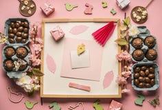 La composición de Pascua, la tarjeta de felicitación, la pluma y los prospectos decorativos en el fondo blanco, alrededor alinear imagen de archivo