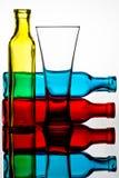 Botellas coloreadas y vidrio reflejados en un espejo foto de archivo libre de regalías