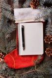 La composición de un calcetín y de un abeto rojos de la Navidad ramifica Fotografía de archivo libre de regalías