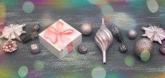 La composición decorativa del fondo de la Navidad de la bandera con la Navidad juega los regalos en un fondo gris del vintage Imagen de archivo libre de regalías