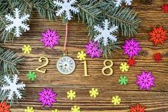 La composición del Año Nuevo con el reloj, los copos de nieve y el abeto ramifica Imágenes de archivo libres de regalías