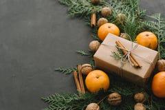 La composición del Año Nuevo de la Navidad con las mandarinas encajona verdes de los conos del pino en la decoración negra del dí Fotografía de archivo libre de regalías