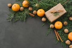 La composición del Año Nuevo de la Navidad con las mandarinas encajona verdes de los conos del pino en la decoración negra del dí Imagen de archivo libre de regalías